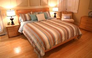 Кровать на ламинате в спальне